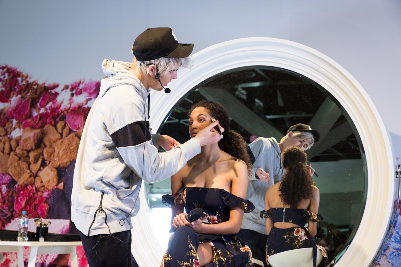 Makeup artist doing vibrant makeup at beauty expo